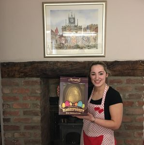 Staff member of Fifteas Vintage Tearooms holding a giant golden Easter Egg