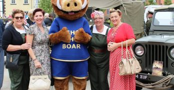 Bishop the Boar with a group of four ladies, dressed in 1940 style clothing