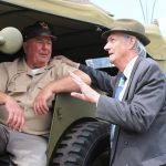 Two gentleman talking next to a military vehicle