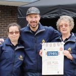 Three Town Team volunteers posed with a 1940s Day poster