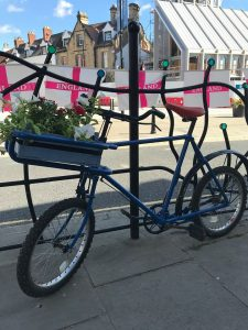 A blue bicycle with a flower basket planter