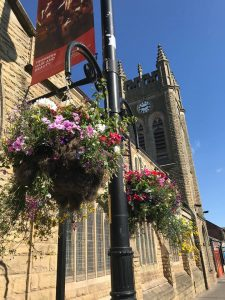 Hanging baskets in bloom outside of The Four Clocks Centre