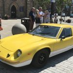 A bright yellow classic car, outsideof Bishop Auckland Town Hall