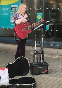 Buskers Day performance by Ami Leigh Boorman on a red acoustic guitar