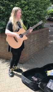 Buskers Day performance by Chloe Smith on acoustic guitar