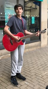 Buskers Day performance by Matthew Tippey on a red acoustic guitar