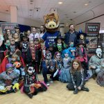 Group photograph of children in Halloween fancy dress, with Bishop the Boar