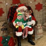 Santa Claus in his Grotto with two small children dressed as Elves