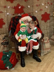Santa Claus in his Grotto with two small children