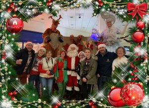Group photograph with Festive boarder; Town Team volunteers with Santa Claus, Elf and two Stilt Walkers