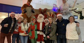 Group photograph of Town Team volunteers with Santa Claus, Elf and two Festive Stilt Walkers