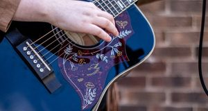 A closeup of a black acoustic guitar with floral decoration