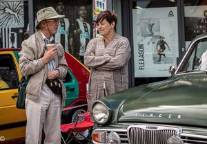 A man and woman stood next to an olive green Singer classic car
