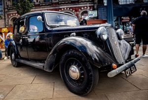 A gloss black classic car in the Market Place