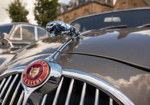 A closeup of the hood ornament of a metallic grey Jaguar