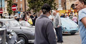 A man pointing towards a sky blue Jaguar E Type with its bonnet open