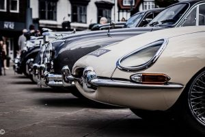 A uniformed lineup of classic cars parked in the Market Place