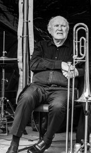 A black and white photograph of One of the Tees Valley Jazz Men with a trombone