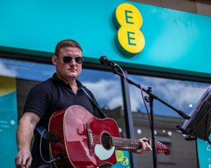Busker Kev playing a red acoustic guitar outside of EE store