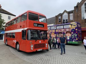 A classic United red double decker bus and Big Purple Play behind