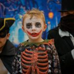 A child dressed up for Halloween with two men in bhe background dressed in black masquerade
