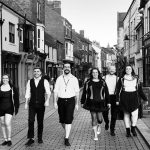 A black and white photograph of a group of performers walking up Fore Bondgate