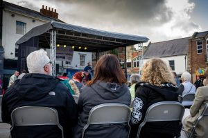 A crowd of people sat watching a singer who is playing acoustic guitar on stage