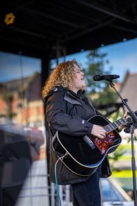 Amy Leigh Boorman singing and playing acoustic guitar on stage