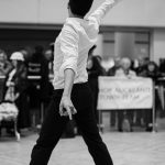 A black and white photograph of a man dancing in the Newgate Shopping Centre