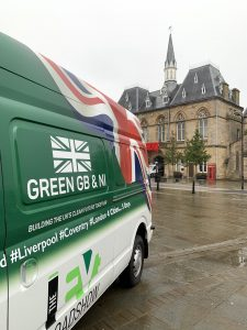 A side view of the white and green EV Roadshow electric van in the Market Place
