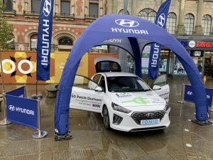 A white Hyundai Ioniq electric car with blue Hyundai branded marquee and banners