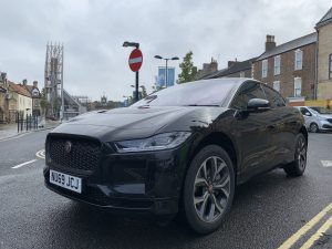 A gloss black electric Jaguar stationery at a junction
