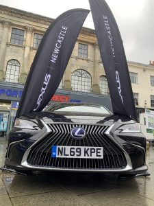 A gloss black electric Lexus car in the Market Place