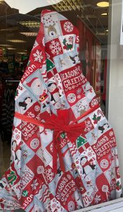 An Advent Window display covered up in red Christmas wrapping paper with a red bow